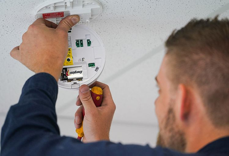 Electrician installing a new smoke alarm in Caringbah